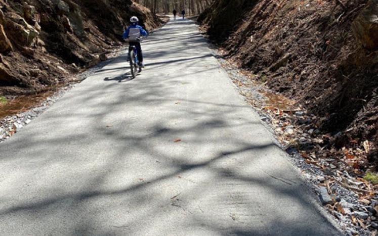 bicyclist on stone-dust rail trail